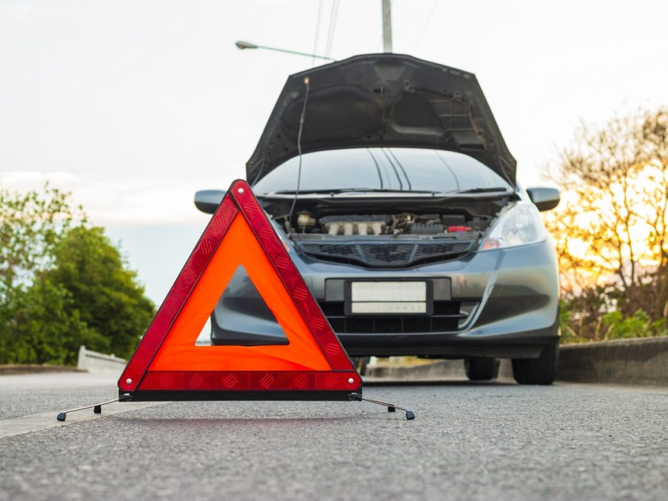 Roadside triangle in front of stalled car on side of road