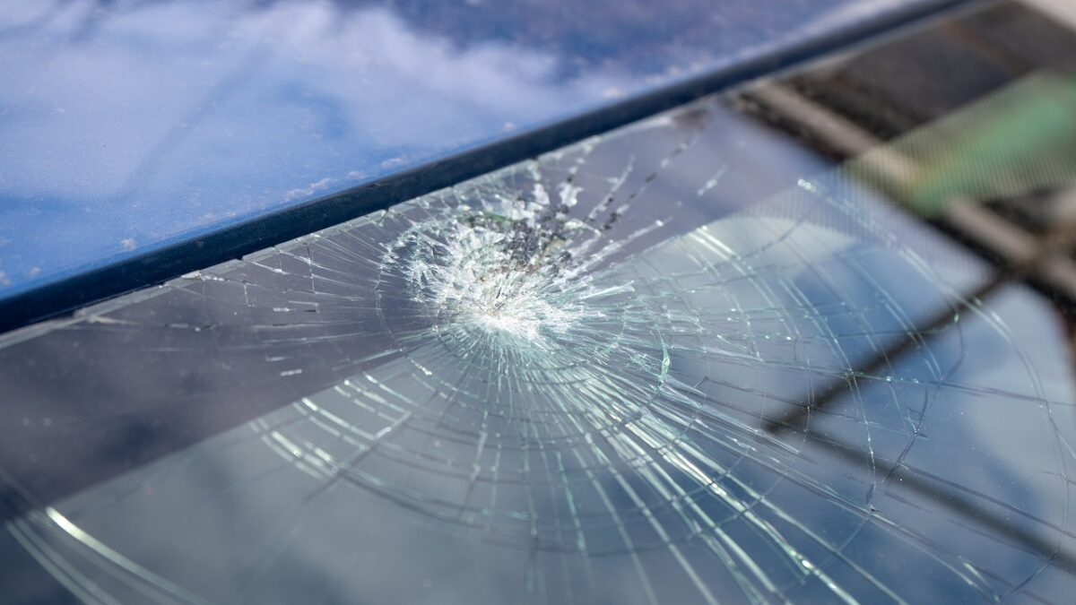 Broken windshield with a lot of cracks and small glass pieces